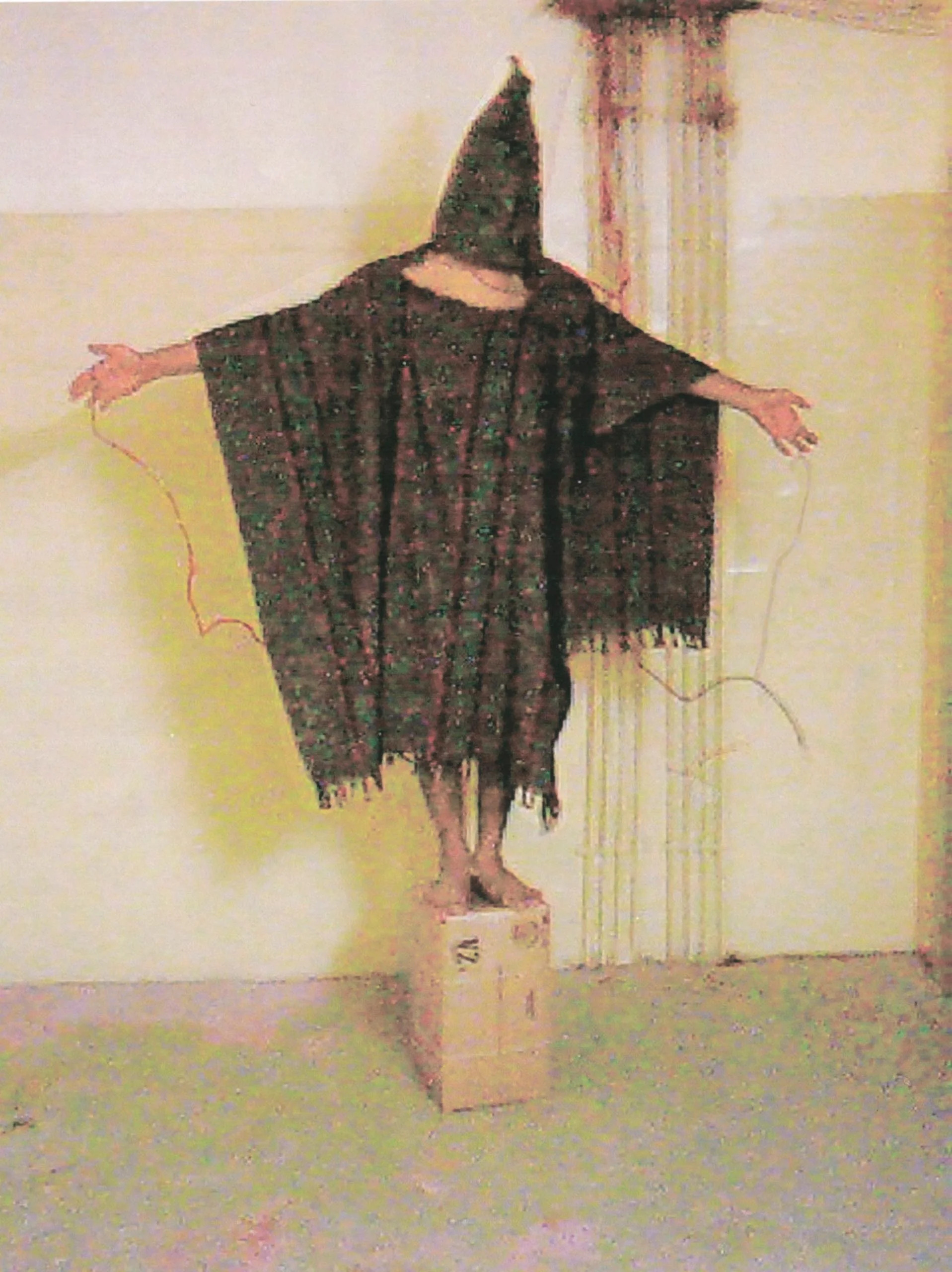 A hooded and wired Iraqi prisoner, believed to be Satar Jabar, who reportedly was told that he would be electrocuted if he fell off the box.