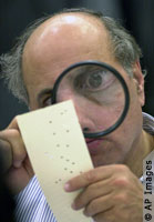 An election worker closely examines a Florida ...