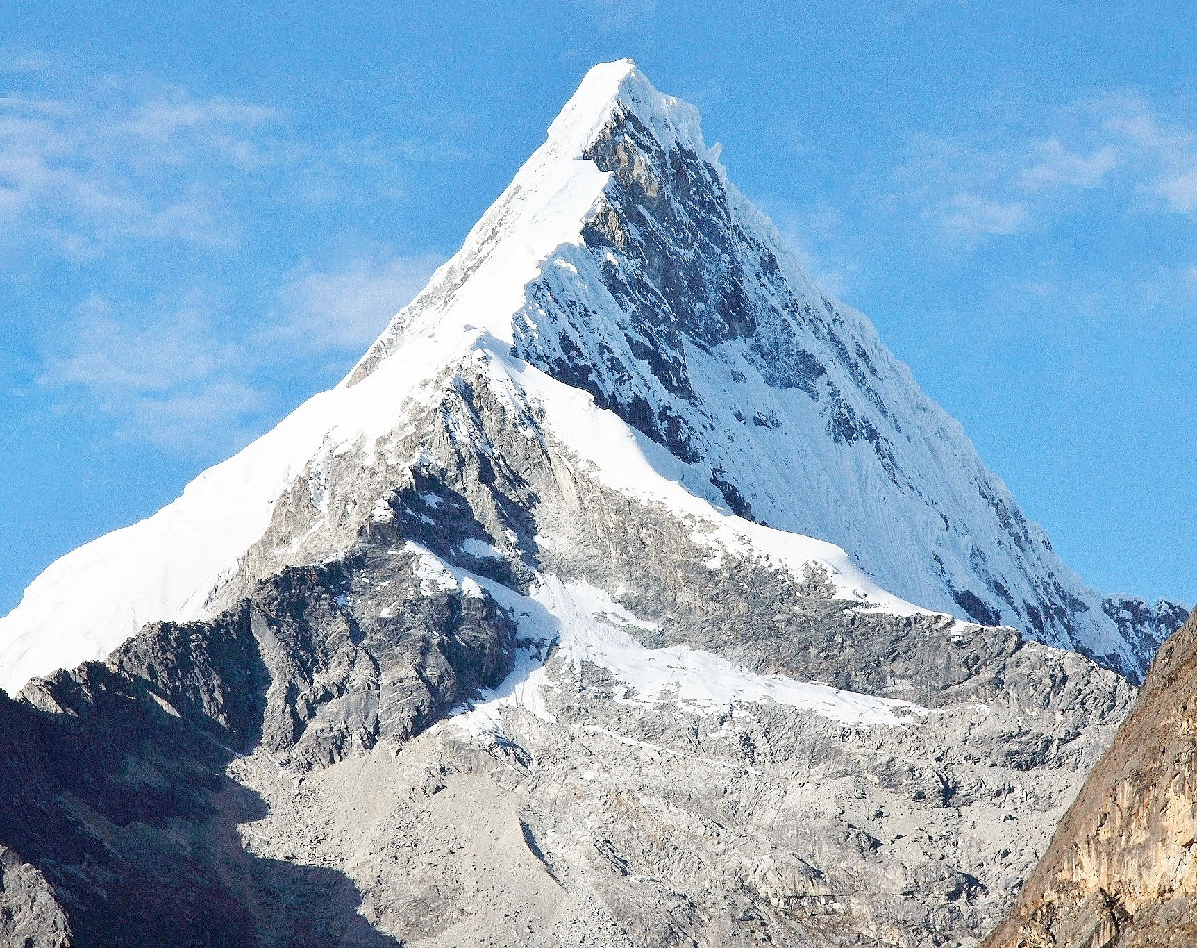 We see a mountain shooting above a cloud deck below. Artesonraju Wikipedia