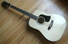 Thin, dark pickguard on acoustic guitar