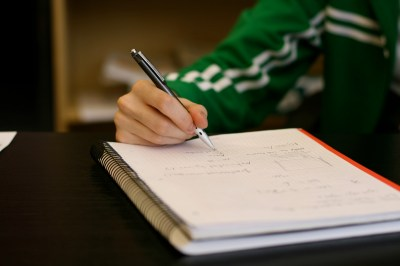 A person writing notes in a book