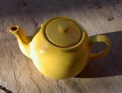 English: A yellow ceramic teapot against a sto...
