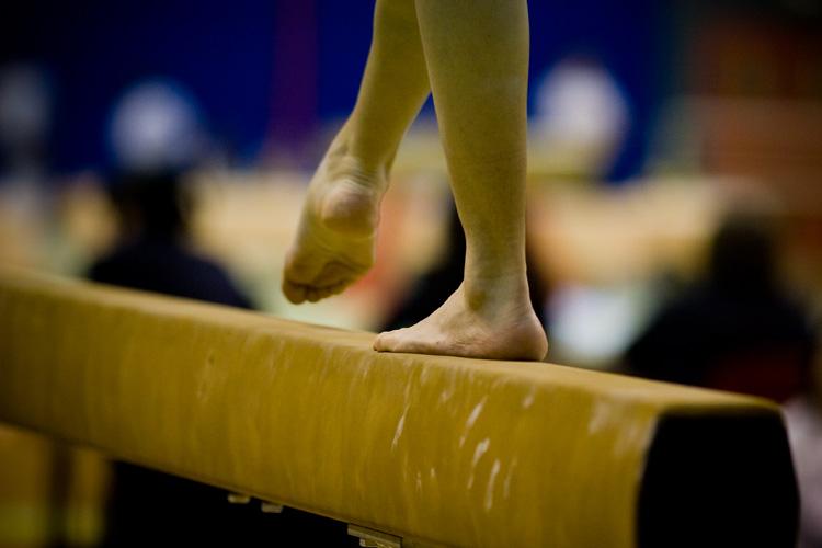 Gymnast feet on beam.
