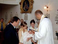 English: A Roman Catholic priest baptizes an i...
