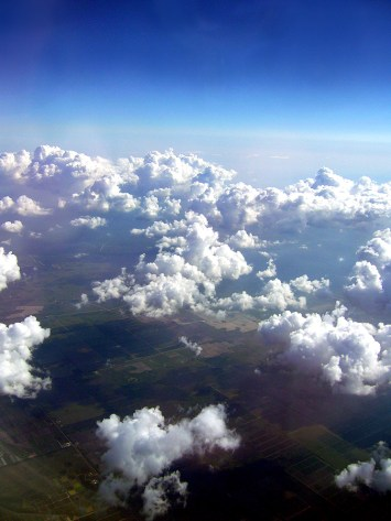 Picture of some clouds, sky and earth taken from an airplane