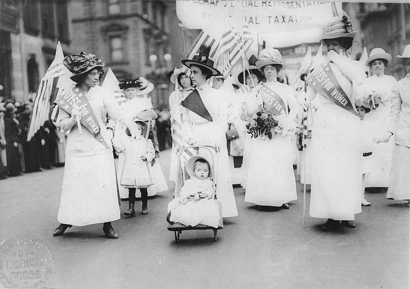 A black and white photo of a crowd of women carrying flags and wearing sashes that say