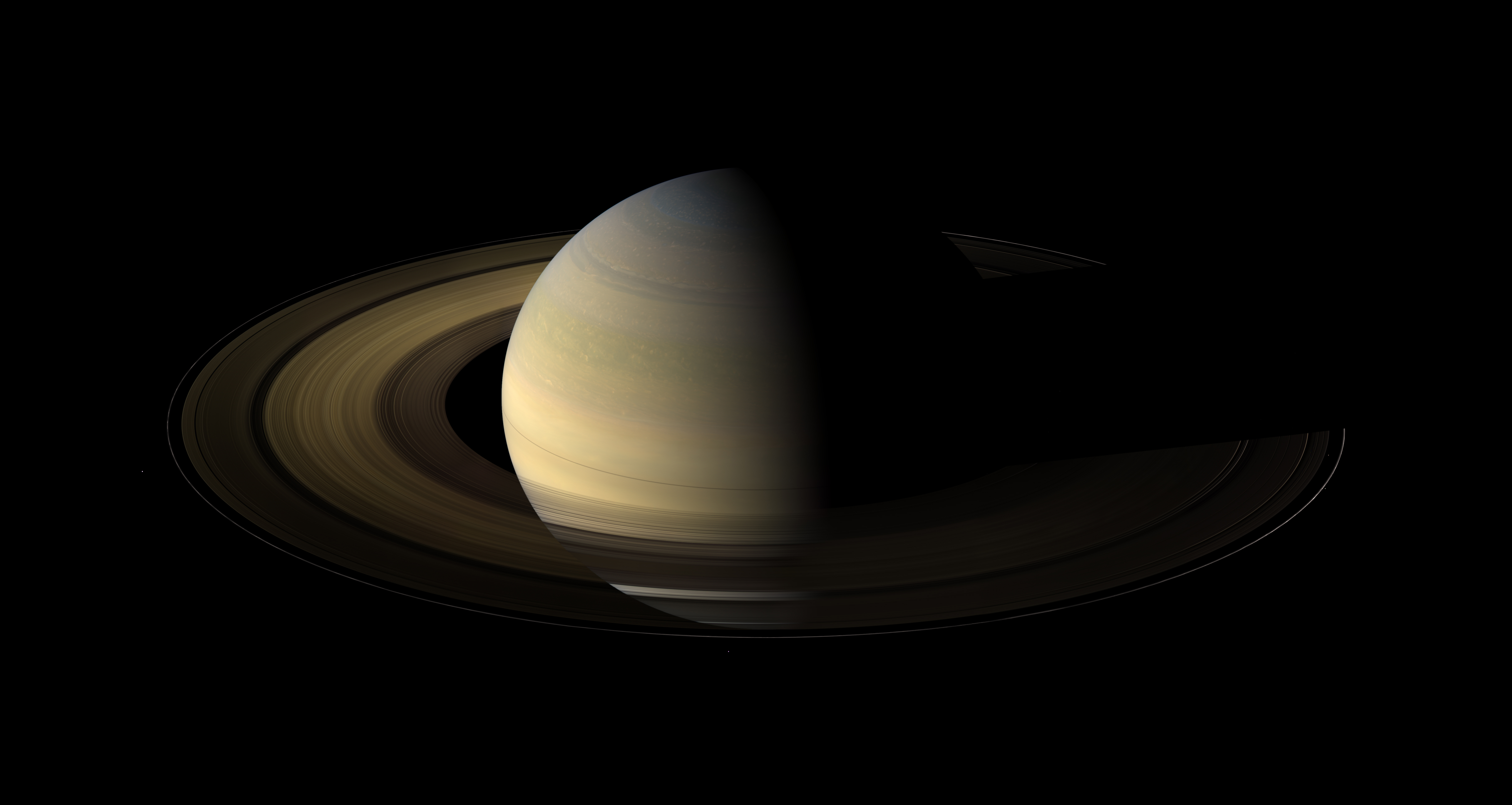 Saturn, its rings, and a few of its moons.jpg