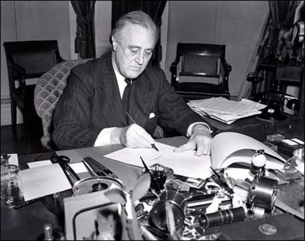 FDR signs H.R. 1946, the lend-lease bill to give aid to Britain and China