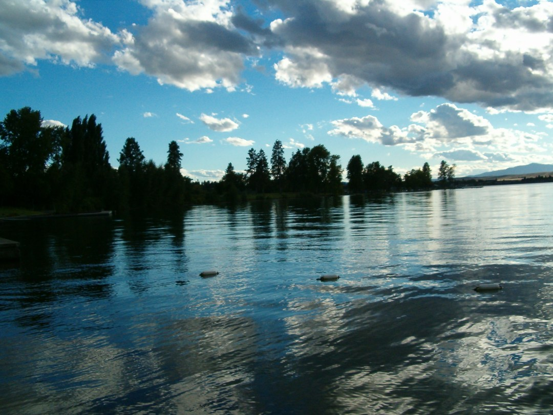 Some clouds over Flathead Lake in Polson, Montana as the sun is setting- surreal places to visit