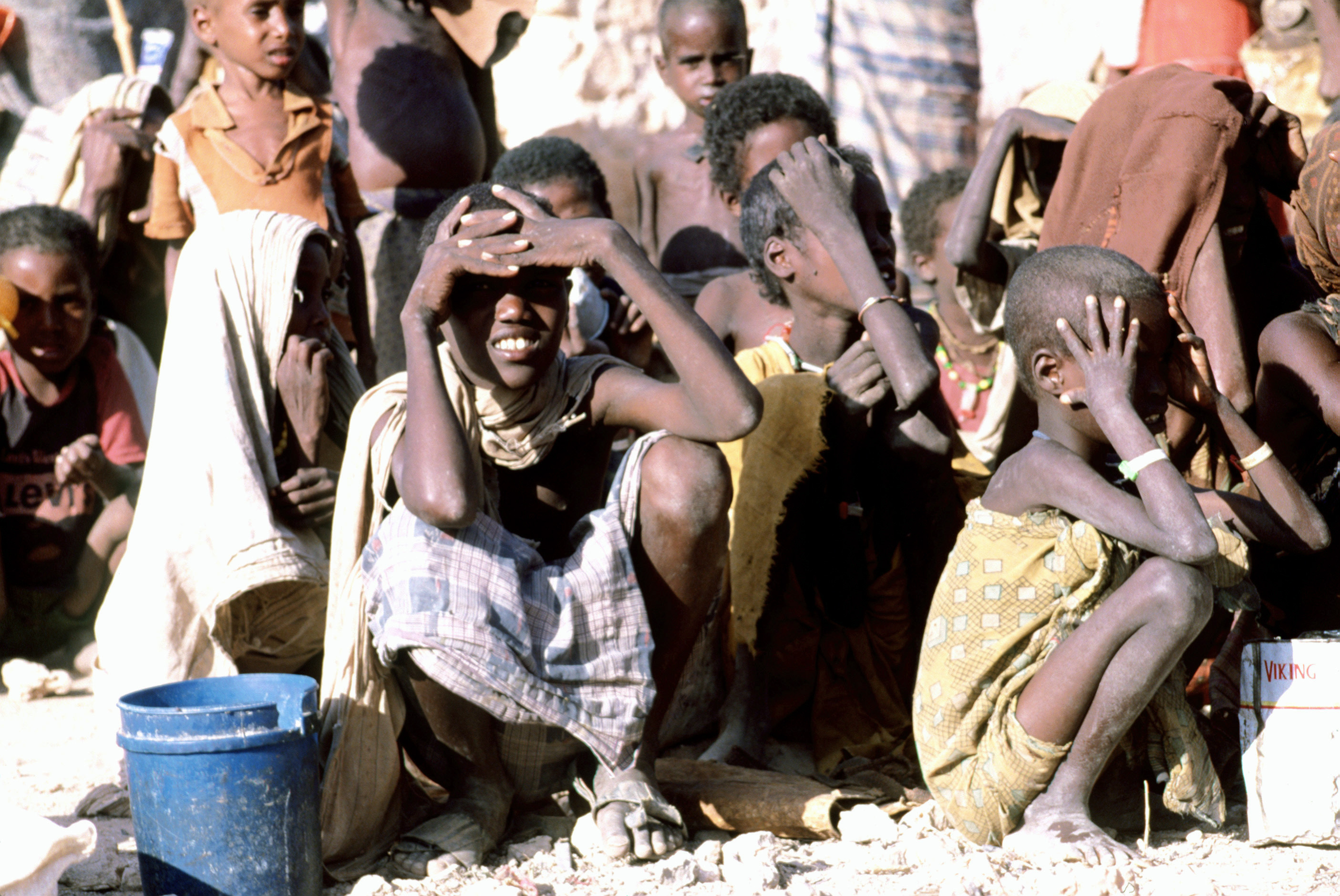 Somalians sit in the sun as they wait for food provided during Operation Provide Relief, Somalia