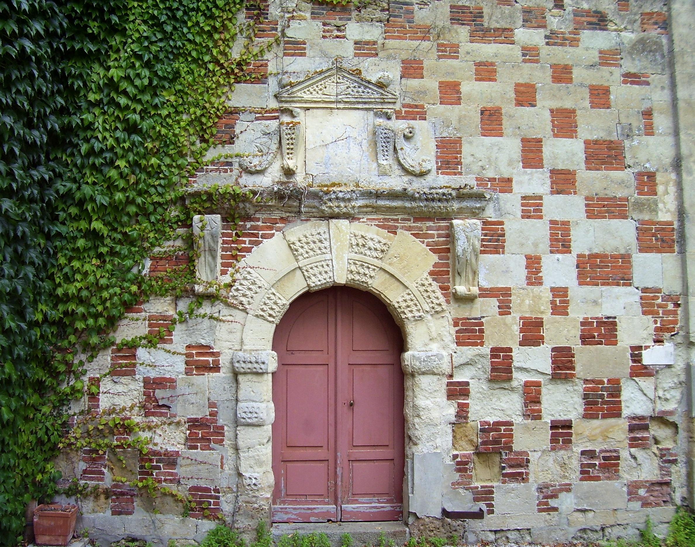 Eingang an der Kirche, dieser Teil erinnert schon sehr an das Schloss, auch wenn die Backsteine nicht grün sind. Eigenes Foto (auf commons), Lizenz:public domain