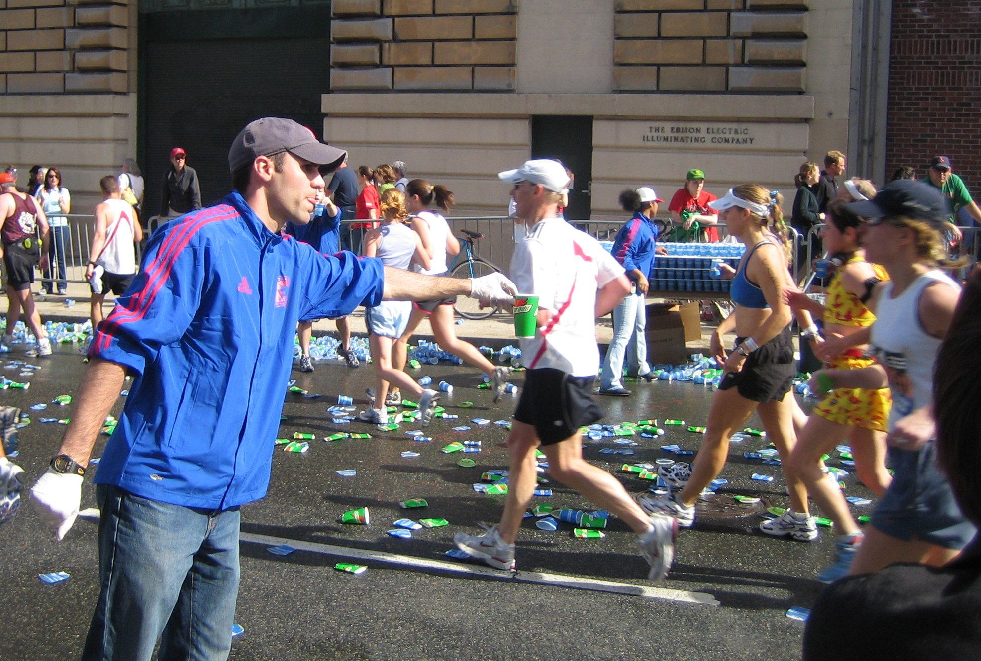 A volunteer hands out fluids at a marathon wat...