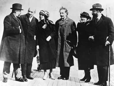 Grupo ocasional composto de quatro homens e duas mulheres em pé sobre um pavimento de tijolos.