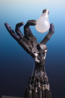Robotic hand holding a lightbulb.