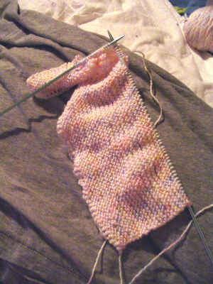 Flat knitting. The loops on the metal needle a...