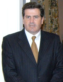 The candidate, dressed in a dark suit and coral-colored tie, standing in front of a white wall and a decorative cloth hanging.