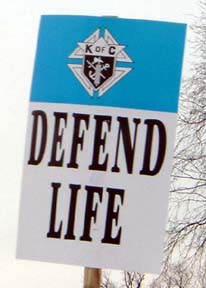 A photograph of a placard at the March of Life that reads defend life on the bottom with the emblem of the Order in a blue band on top.