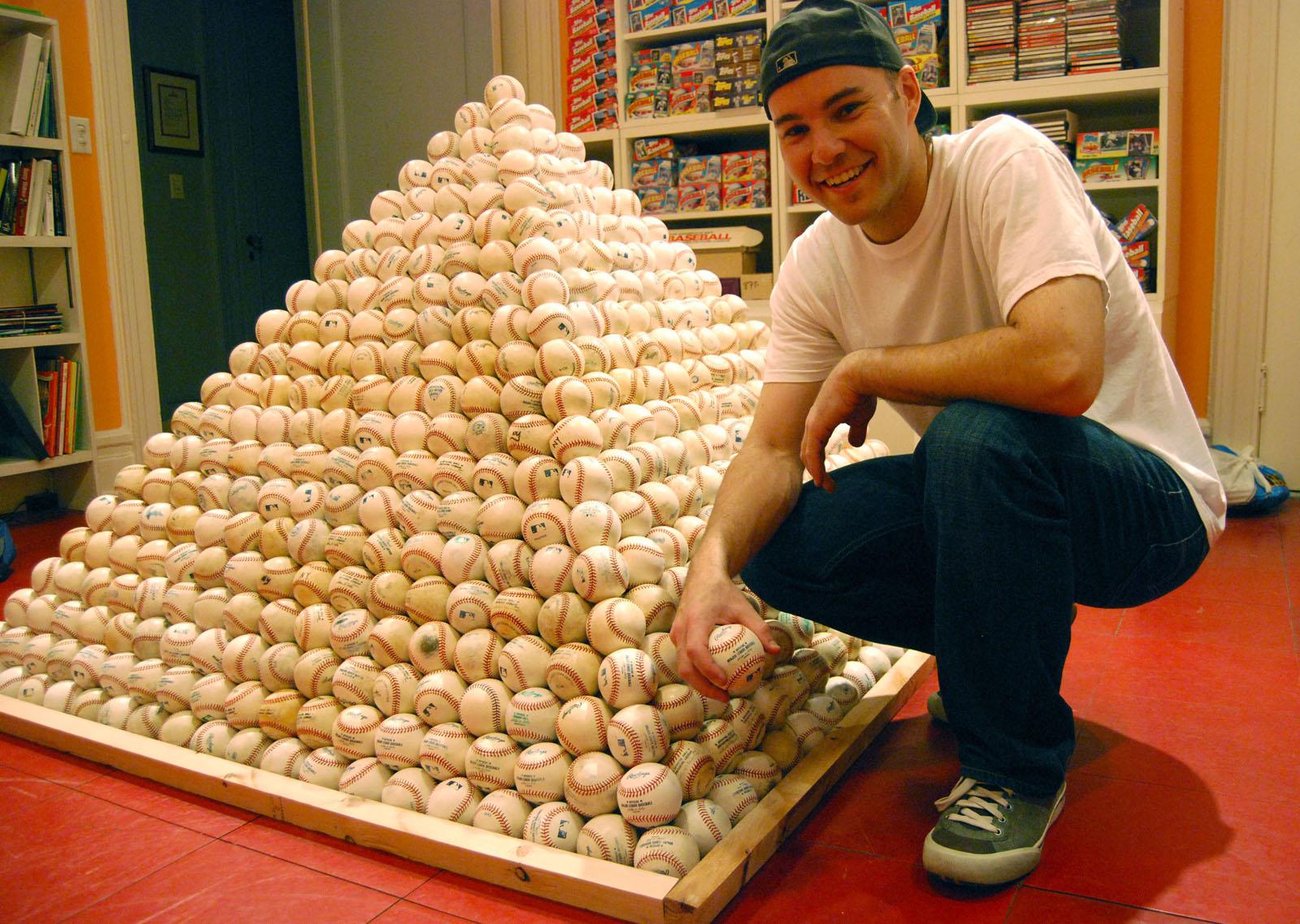 https://i1.wp.com/upload.wikimedia.org/wikipedia/commons/f/f5/Zack_Hample_posing_with_a_pyramid_of_baseballs.jpg