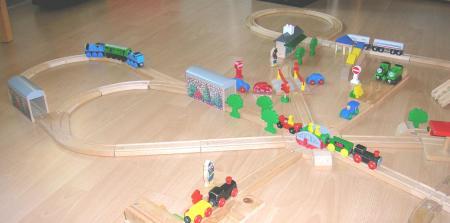 Tren y vías de madera de juguete montando una ciudad de forma radial.