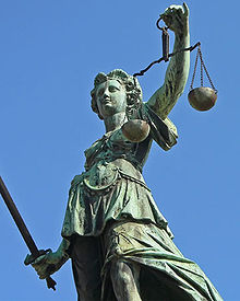 Statue représentant la Justice portant à main droite le glaive et à main gauche, bras en l'air, la balance.