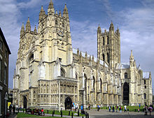 Large yellow stone ornate building with buttresses and square central tower.