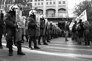 Greek riot police standing next to protesters.