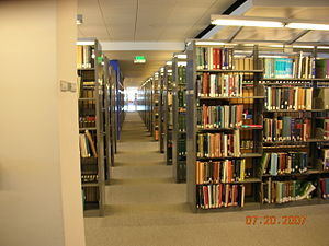 A pathway between rows of bookshelves on the e...