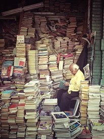 Man reading among a large pile of books