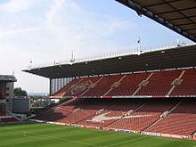 Sebuah pacuan di stadion olahraga. Kursi didominasi merah.