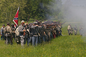 Confederate reenactors fire their rifles durin...