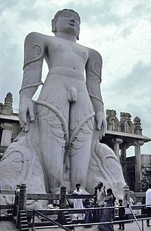 Giant grey stone statue of nude man with vines climbing legs to his arms
