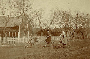 3 women on bicycles on unpaved country road, U...