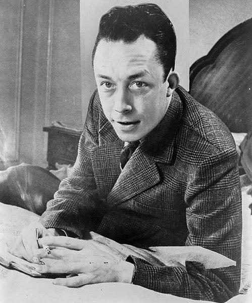 File:Albert Camus, gagnant de prix Nobel, portrait en buste, posé au bureau, faisant face à gauche, cigarette de tabagisme.jpg