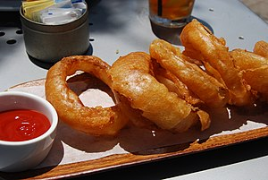 Deep-fried onion rings arranged in a line on a...