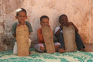 Young boys taking Qur'an lessons from wooden t...