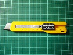 Heavy duty OLFA SL-1 cutter against a cutting mat.
