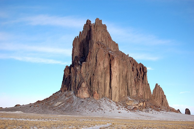 The Shiprock, a plug from an ancient volcano, left after the mountain eroded away. Near Shiprock, New Mexico, on the Navajo Reservation. Wikipedia image by Bowie Snodgrass
