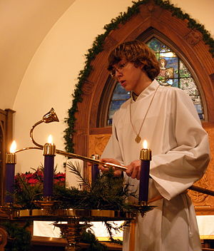 English: An acolyte lighting Advent candles on...