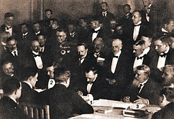 Three formally attired men at a conference table sign documents while 32 others look on.