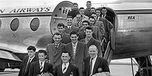 Photographie en noir et blanc de plusieurs personnes en costume et pardessus sur les marches d'un avion.