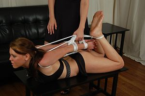 A woman is hogtied. Note the carrying handle o...