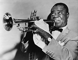 A picture of Louis Armstrong. Short-haired, black man in his fifties blowing into a trumpet. He is wearing a light-colored sport coat, a white shirt and a bow tie. He is faced left with his eyes looking upwards. His right hand is fingering the trumpet, with the index finger down and three fingers pointing upwards. The man's left hand is mostly covered with a handkerchief and it has a shining ring on the little finger. He is wearing a wristwatch on the left wrist.