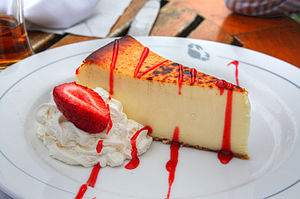 Cheesecake with strawberry and whipped cream.