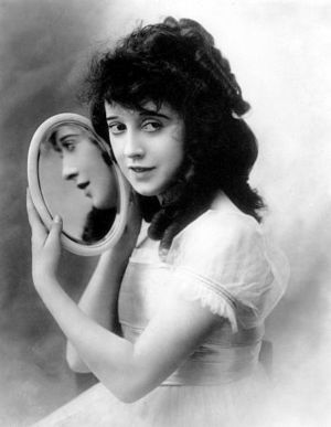 Actress Mabel Normand holding a small round mi...