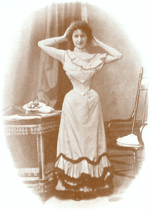 A woman models a corset in this 1898 photograph.