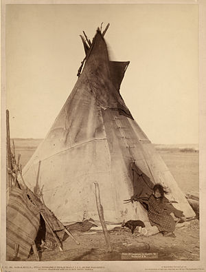 A young Oglala girl sitting in front of a tipi...