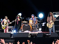 A photograph of four members of The Red Hot Chili Peppers performing on a stage