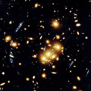 Astronomia extragaláctica: lente gravitacional. Esta imagem captada pelo Telescópio Hubble mostra vários objectos azuis em forma de espiral que na verdade são imagens múltiplas da mesma galáxia. A imagem original da galáxia foi duplicada pelo efeito de lente gravitacional causado pelos clusters de galáxias el�pticas e em espiral de cor amarela que aparecem no centro da fotografia. A lente gravitacional deve-se ao poderoso campo grav�tico que o cluster cria e que curva, distorce e amplifica a luz de objectos mais distantes.