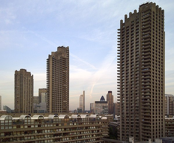 Photograph of tall, concrete towers seen from the Barbican, with other local buildings along the skyline.