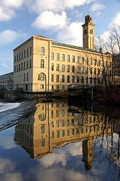 A stone factory stands against a vivid blue sky, its reflection mirrored in the waters below.